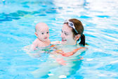 Young mother and baby son in a swimming pool — Stock Photo