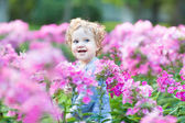 Curly baby girl  in the field — Stock Photo