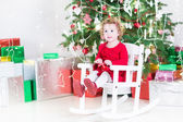Toddler girl under a beautiful Christmas tree — Stock Photo