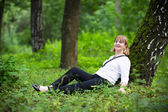 Woman relaxing under a old tree — Stock Photo