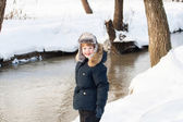 Cute boy walking along a frozen brook — Stock fotografie
