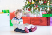 Funny little toddler girl opening her Christmas present — Photo