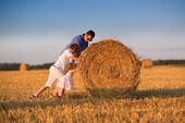 Young father and two children in a hay bales field — Stock Photo