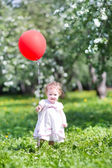 Baby girl playing with a red balloon — Stock Photo