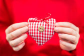Hands of a child holding a plaid red-white textile heart — Stock Photo