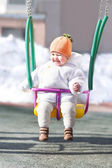 Baby in a swing on a sunny winter day — Stock Photo