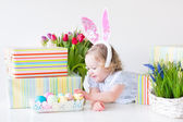 Toddler girl with bunny ears playing with Easter presents — Stock Photo