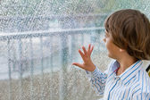 Smiling boy watching the rain — Stock Photo