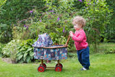 Baby girl playing with a  doll stroller — Stockfoto