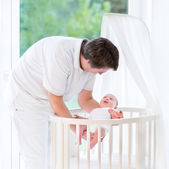 Young smiling father putting his newborn baby — Stock Photo