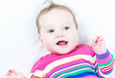 Baby girl in a knitted colorful dress — Stock Photo
