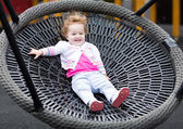 Baby girl relaxing on a swing — Stock Photo