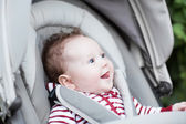 Baby sitting in a stroller — Stock Photo