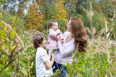 Woman playing with her son and daughter in a field — Stock Photo