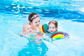 Young active mother having fun in a swimming pool with two kids — Stock Photo