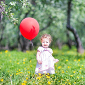 Baby girl playing with a red balloon — Photo