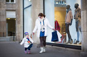 Woman and her toddler daughter enjoying winter sale shopping — Stock Photo