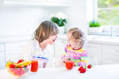 Happy teenager boy and his cute toddler sister having fruit for breakfast — Stock Photo