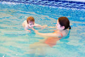 Mother with  baby in the swimming pool — Stock Photo