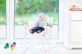 Newborn baby boy in a white rocking chair — Stock Photo