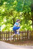 Funny little boy enjoying a swing ride — ストック写真