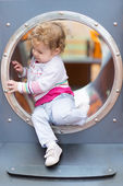 Baby girl sliding on a playground — Stock fotografie