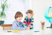 School boy doing his homework and his toddler sister watching him — Foto Stock