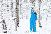 Cute boy walking in a snowy forest — Stock Photo