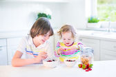 Teenager boy and his sister having fruit and cereal with strawberry for breakfast — Stock Photo