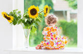 Baby girl sitting at a window next to beautiful sunflowers — Stock fotografie