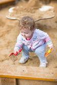 Baby girl digging in sand — Zdjęcie stockowe