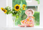Baby girl sitting at a window next to beautiful sunflowers — Stock Photo