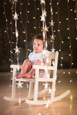 Toddler girl relaxing in a white rocking chair — Stock Photo