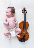 новорожденных девушка, лежа рядом со скрипкой — Стоковое фото