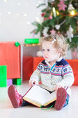 Funny little toddler girl opening her Christmas present — Stockfoto