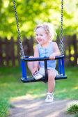 Happy laughing toddler girlenjoying a swing ride — Stock Photo