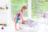 Toddler girl in a pink dress playing with her teddy — Stock Photo