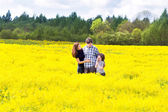 Family in a field of yellow flowers — Stok fotoğraf
