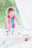 Toddler girl playing with newborn brother — Stock Photo