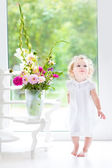 Baby girl playing next to a big window — Stock Photo