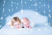 Newborn baby and toddler sister playing on a white bed — Stock Photo