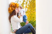 Mother with maple leaves wreath kissing her baby — Stock Photo
