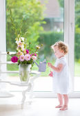 Baby girl smelling beautiful flowers — Stock Photo