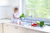 Toddler girl washing vegetables in a kitchen sink — Stock Photo