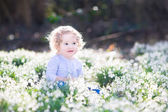 Girl playing with first spring flowers — Stock Photo