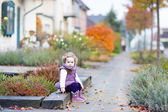 Toddler girl sitting on the front yard of  house — Stock fotografie
