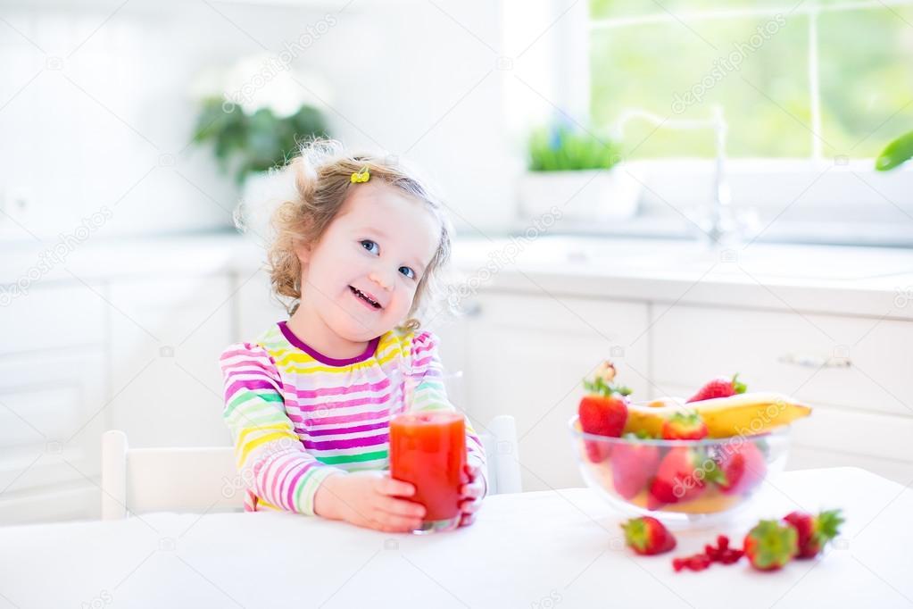 Chica Del Niño Desayunando Tomando Jugo Y Comiendo Copos