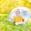 Baby girl under a colorful umbrella — Stock Photo