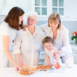 Grandmother baking an apple pie with her family — Stock Photo