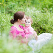 Mother and her baby daughter relaxing in the garden — Stock Photo